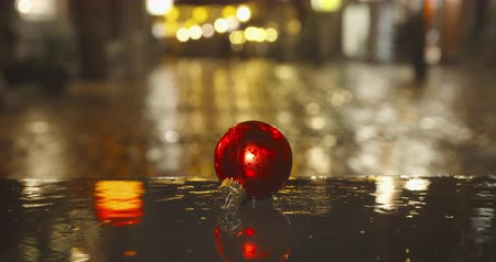 Rainy christmas days - a christmas bulb lying on the ground of a christmas-lit pedestrian-only shopping street - ProRes Stock mozgókép