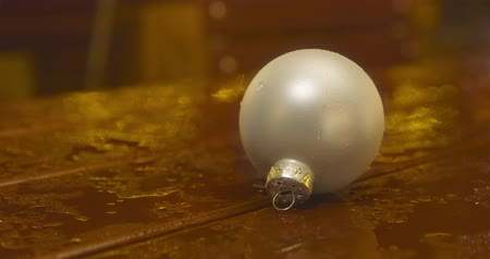 A Christmas bulb placed on a table after a rain shower - ProRes