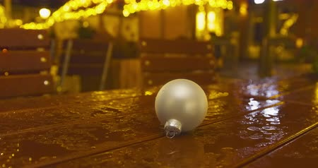 Rainy Christmas market - a Christmas bulb - a wooden table placed on a Christmas market - ProRes