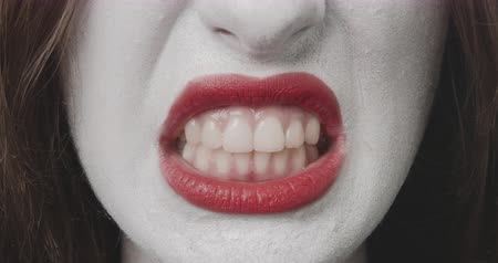 rehearsing : Baring the teeth - close-up of a teenage girl, who is making Halloween or a costume party. Rehearsing different facial expressions, she is baring her teeth - ProRes