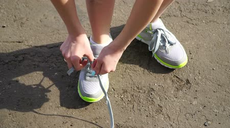 buty sportowe : girl stopped running to tie the laces on running shoes. fitness girl training outdoors