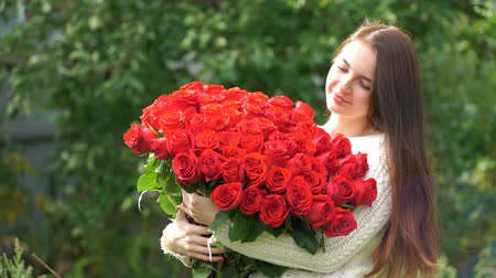valentin nap : footage woman holding a bouquet of roses outdoors. 4k