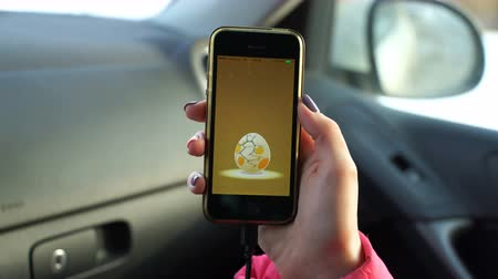 тыкать : Samara, Russia - February 21, 2017: woman playing pokemon go on his iphone. pokemon go multiplayer game with elements of augmented reality. Second generation of Pokemon.