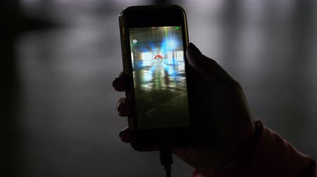 realidade : Samara, Russia - February 21, 2017: woman playing pokemon go on his iphone. pokemon go multiplayer game with elements of augmented reality. Second generation of Pokemon. Aipom was caught. Vídeos