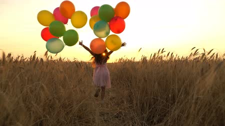 gidip : young girl in the dress with colorful ballons is running across the field.