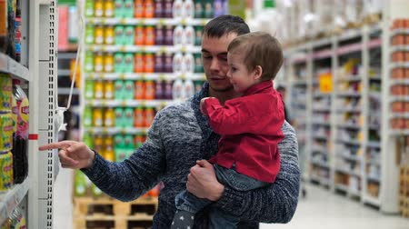 supermarket food : Footage father and son buy water or juice in a store. Stock Footage
