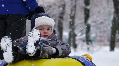 trubky : boy of two years rolling on tubing in the park in winter.