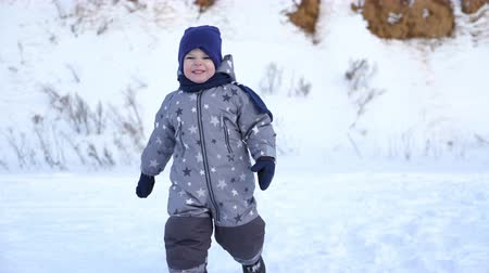 снежинки : boy of two years walks in winter.