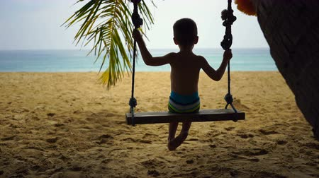 boy of two years swings on a swing on the beach near the ocean.