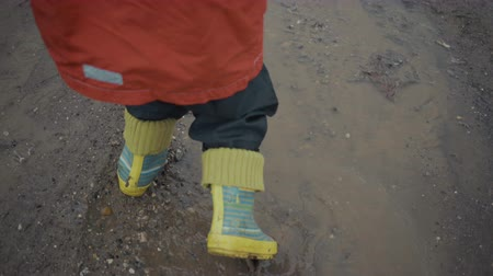 boy walks through the puddles and mud in the spring. Stock Footage