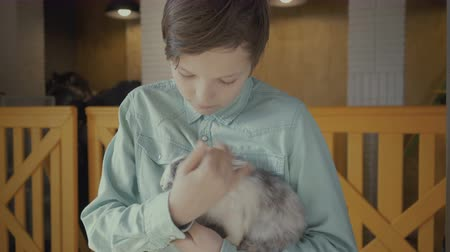 boy holds a rabbit in his hands on a farm.