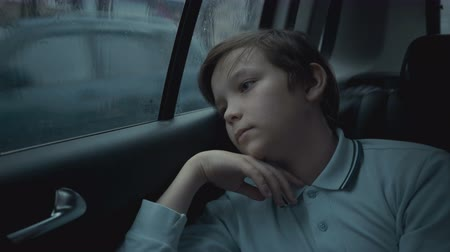 Sad, unhappy young boy riding in car through city during rainy day Stock Footage