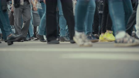 низкий : People pedestrians walks across a busy city street. Стоковые видеозаписи