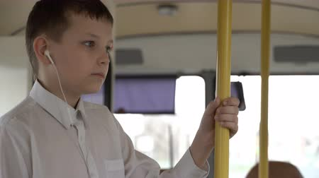 dull : close-up shot of a young boy traveling by bus through city. He listens to music. Stock Footage