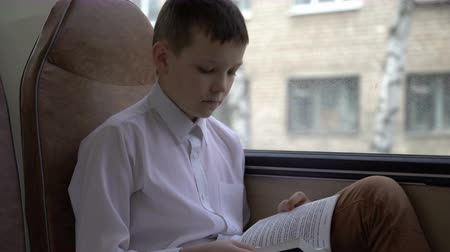 alfabetização : shot of a young schoolboy traveling by bus through city and reads a book. Stock Footage