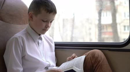alfabetização : shot of a young schoolboy traveling by bus through city and reads a book. Vídeos