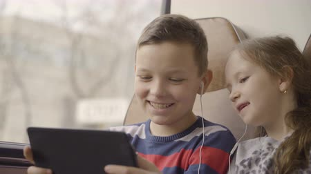 dull : close-up shot of a young boy and girl traveling by bus through city, watching movie on computer tablet.