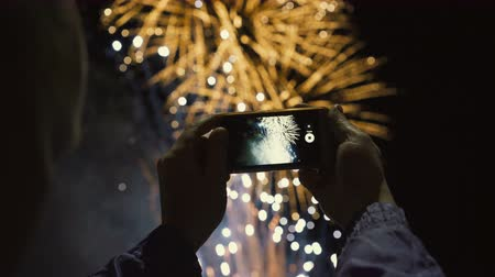 glow pyrotechnics : Silhouette of a man photographing fireworks at night sky. Beautiful salute in honor of the holiday. Stock Footage