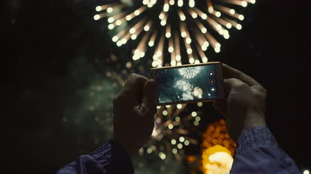 fiesta : Silhouette of a man photographing fireworks at night sky. Beautiful salute in honor of the holiday. Stock Footage