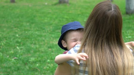 mateřský : Son rushes into mothers arms at park.