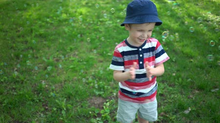 outdoor : Happy little boy blowing soap bubbles in park