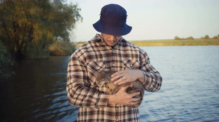 kittens playing : young guy stroking a cat on the nature near the lake. Stock Footage