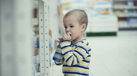 vozíky : Little boy in the supermarket choose a bottle of mineral water.