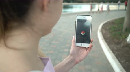 poke : Samara, Russia - July 11, 2018: woman playing pokemon go on his iphone. pokemon go multiplayer game with elements of augmented reality. Catching the Mew pokemon