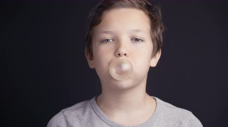 fodormenta : Footage boy make bubble with chew on dark background. Stock mozgókép