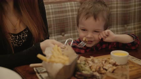 boy of two years is eating french fries in a restaurant. Stock mozgókép