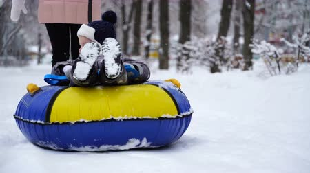 boy of two years rolling on tubing in the park in winter.