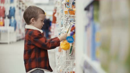 Little boy is standing of the shop and choosing toys