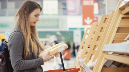 woman buying fresh bread in a supermarket mall.