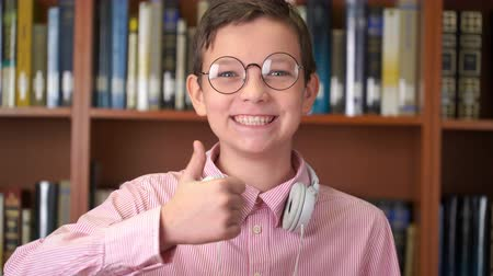 portrait shot of the cute schoolboy standing near the bookshelf in the library and doing thumb up Stock Footage