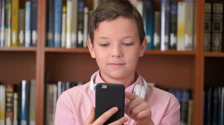 portrait shot of the cute schoolboy with smartphone standing near the bookshelf in the library