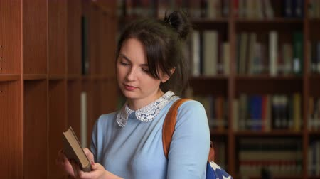 beautiful pretty woman chooses a book to reading in a library.