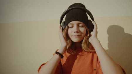 pomarańcza : cute young girl listening music in headphones, urban style, stylish hipster teen in black hat listen music and smile infront of yellow wall, orange crazy street style