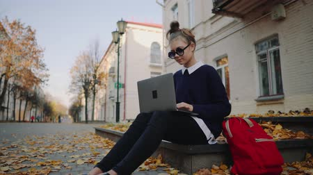 wristband : Pretty hipster teen girl sitting on a sidewalk on autumn city street and working laptop computer. Schoolgirl using notebook outdoor. Beautiful autumn weather.