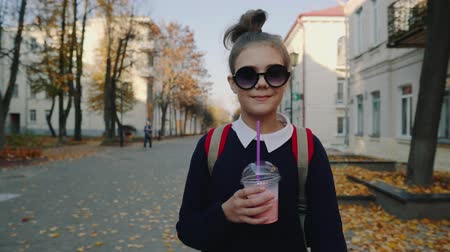 turmix : Pretty hipster teen with red bag drinks milkshake from a plastic cup walking street between buildings. Cute girl in sunglasses drinks a beverage through a straw.