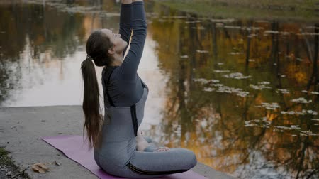 jezero : Young woman practicing yoga outdoors. Female meditate outdoor infront of beautiful autumn nature.