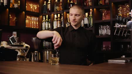 джин : Young barman in bar interior pouring whiskey in glass and bringing it for visitors