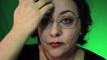 mature latina woman puts on glasses with green background