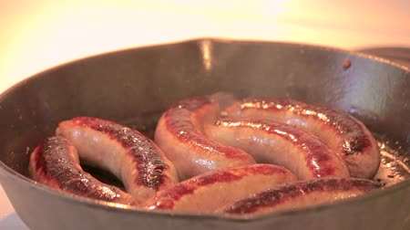 fried : cooking brats in cast iron pan Stock Footage