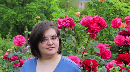 vigyorgó : girl with glasses in front of roses Stock mozgókép