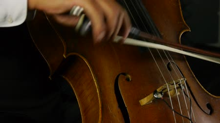 instrumentos : Tight shot from below of cello strings being played