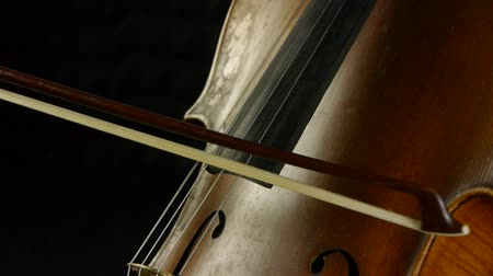 cselló : Cellist playing on cello. Musician in a darkened background.