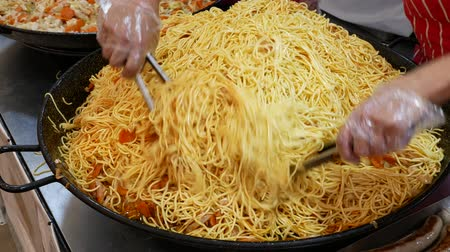 there : Chinese noodles with chicken and vegetables. Frying noodles on a large pan. Street food at the stand. Stock Footage