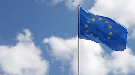 bizottság : The flag of the European Union in the wind with clouds in the background.