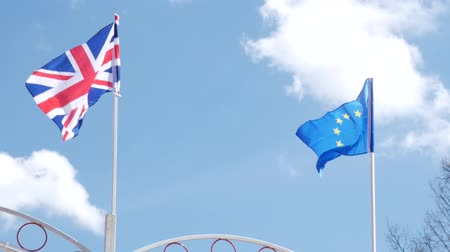 glória : The British flag and the flag of the European Union on a blue sky background.