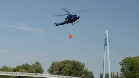 Fire brigade rescue helicopter carries water in the tank.